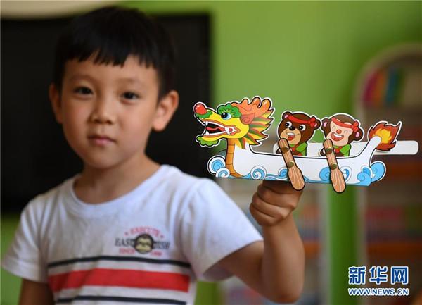 5月23日,一名儿童在展示其剪贴制作的龙舟.  新华社记者 王晓 摄